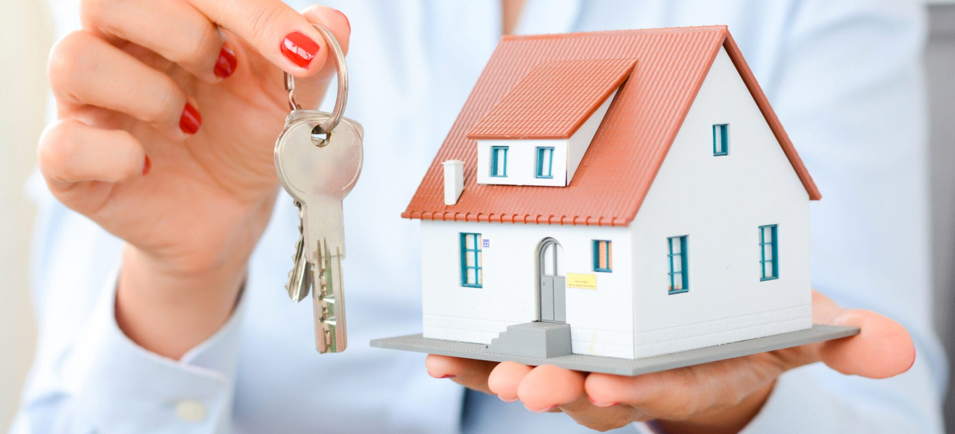 uying a house concept with woman hands holding a model house and house keys